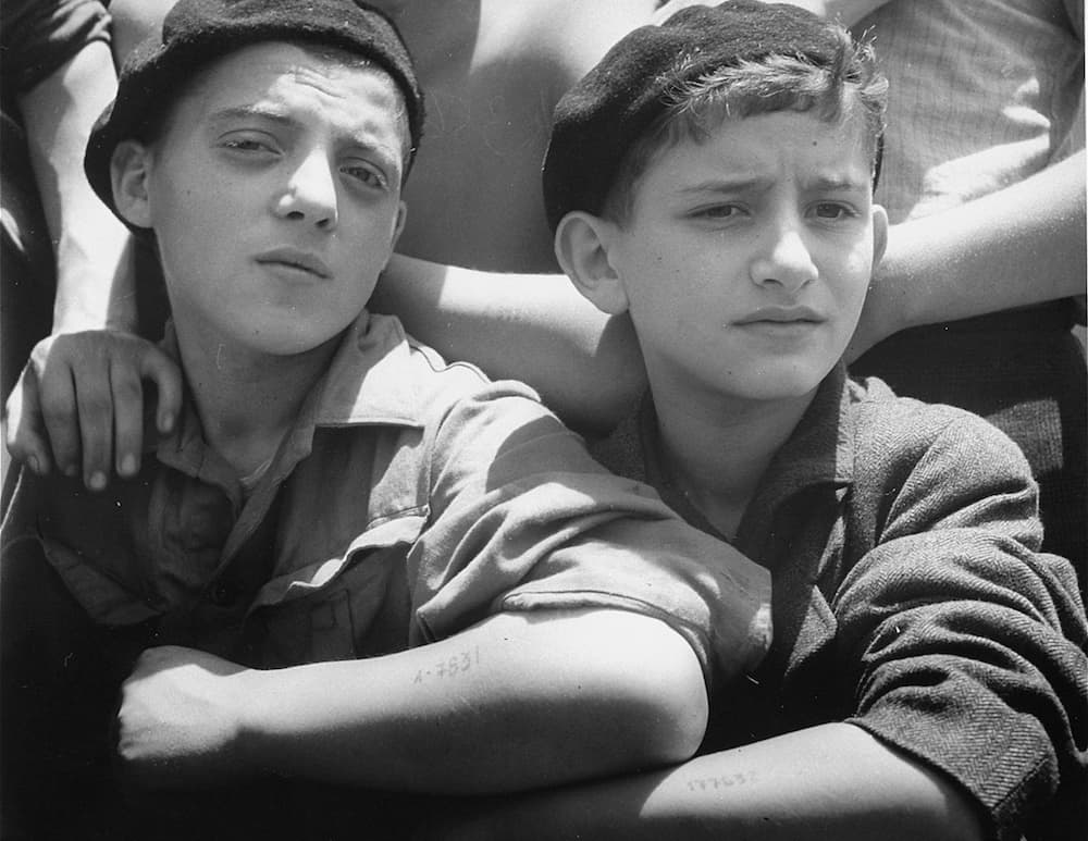 Two young child survivors on board the SS Mataroa display their tattooed arms. ——US Holocaust Memorial Museum, courtesy of Israel Government Press Office