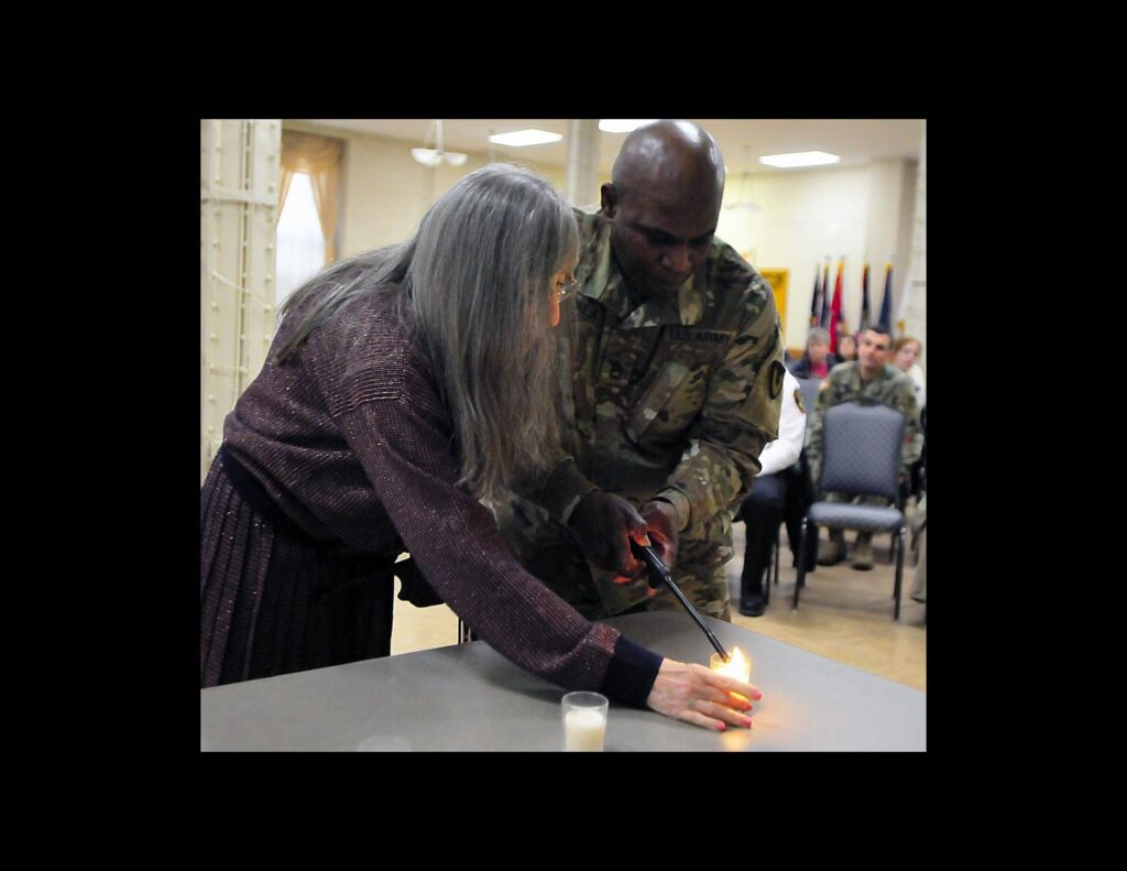 Marguerite Mishkin, Holocaust child survivor, and Sgt. 1st Class, Babatunde Akala, Equal Opportunity adviser, U.S. Army Sustainment Command, light the first candle in a lighting ceremony as part of the observance held at Rock Island Arsenal, Illinois.